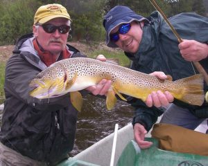 Fishing guide on big hole holding large brown trout